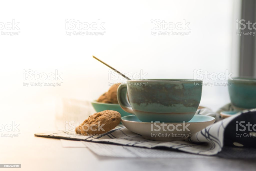 Cup of black coffee with spoon on supported dish on fabric on black and white newspaper is put on hard table in the early morning with bright yellow light and some biscuits for refresh stock photo