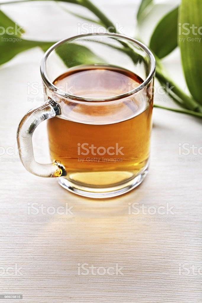 Cup of black tea and green leaves royalty-free stock photo