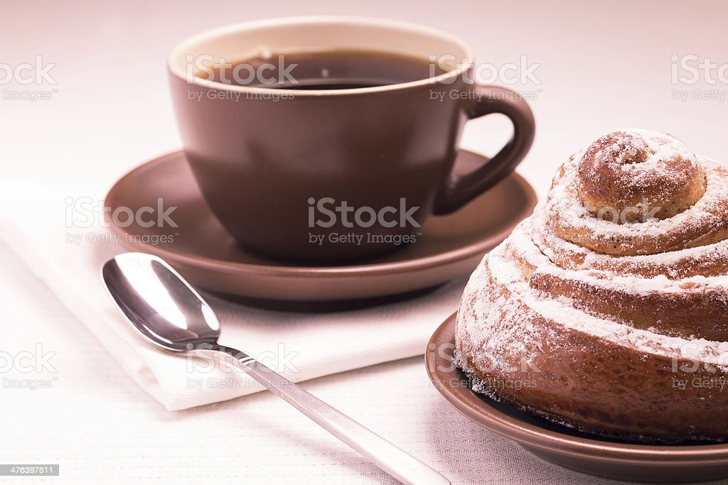 Cup of Black Tea on White Napkin with Sweet Bun royalty-free stock photo