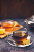 Cup of black tea served with honey and lemon