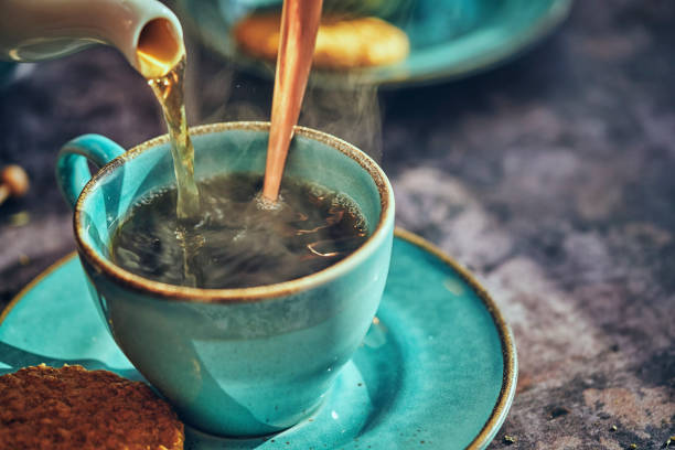 Cup of Black Tea Served with Biscuits Cup of Black Tea Served with Biscuits tea crop stock pictures, royalty-free photos & images