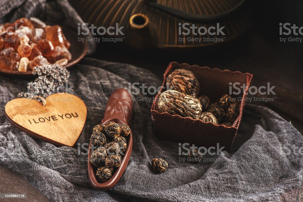 A Cup of brewed black tea. Two ceramic spatulas with caramel sugar and Rolled leaves in a large pearl. Chinese tea from Yunnan. Bi Lo Chun stock photo
