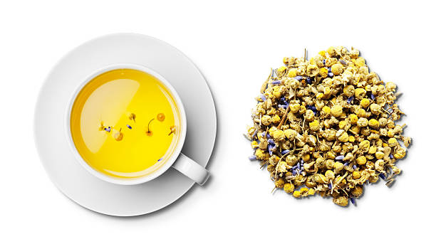 cup of camomile and lavender tea and tea leaves overhead - 甘菊 個照片及圖片檔