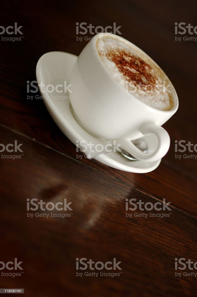 Cup of cappuccino coffee angled on a reflective wood table royalty-free stock photo