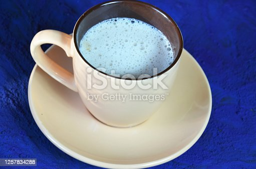 Cup of cappuccino coffee or latte on the dark blue background