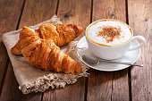 cup of cappuccino coffee with croissants on wooden table