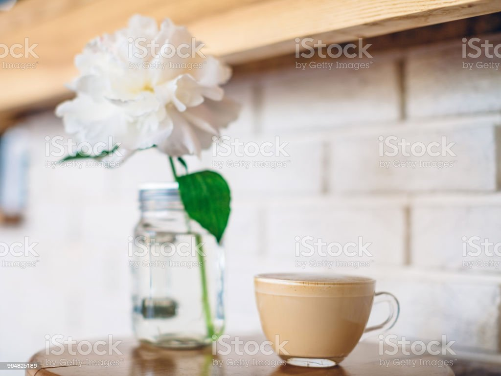 A cup of cappuccino in a cafe on white brick wall background royalty-free stock photo