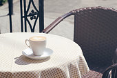 A cup of cappuccino or latte with a pattern on the table with a checkered tablecloth. The table is located on the terrace of a cozy cafe.