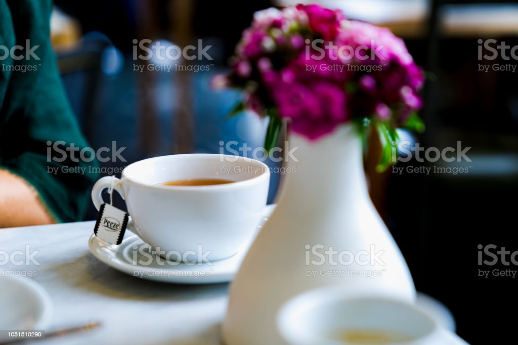 A cup of cappuccino on a white table