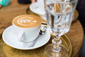 Close up of a cup of cappuccino with a beautiful latte art and a glass of water.