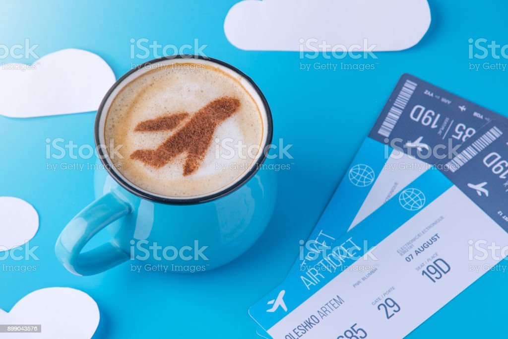 Cup of cappuccino with a picture of the plane on the foam and tickets. Blue sky background with paper clouds stock photo
