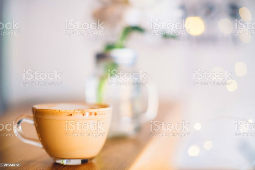 A cup of cappuccino with christmas lights on the bar counter in a cafe royalty-free stock photo