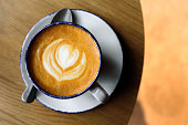 Cup of cappuccino with latte art on wooden table. Beautiful foam, ceramic cup, place for text, top view