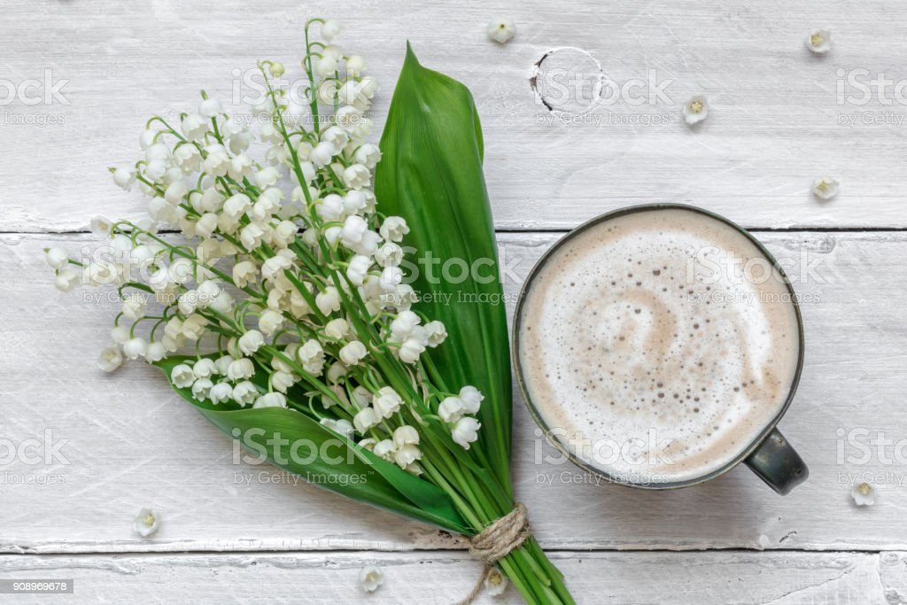 spring lily of the valley flowers bouquet with cup of coffee with...