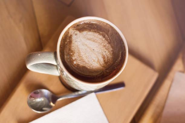 tasse johannisbrot getränk auf holztisch - kaffee protein shakes stock-fotos und bilder