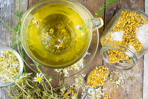 Cup of chamomile tea with dry chamomile flowers stock photo