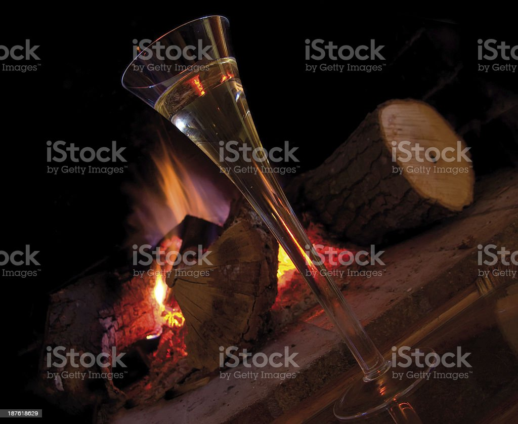 Cup of champagne near fireplace royalty-free stock photo