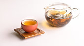 Cup of chinese tea in a lovely traditional tea cup with teapot by the side, isolated.