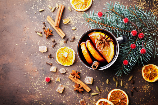 Cup of christmas mulled wine or gluhwein with spices and orange slices on rustic table top view. Traditional drink on winter holiday.
