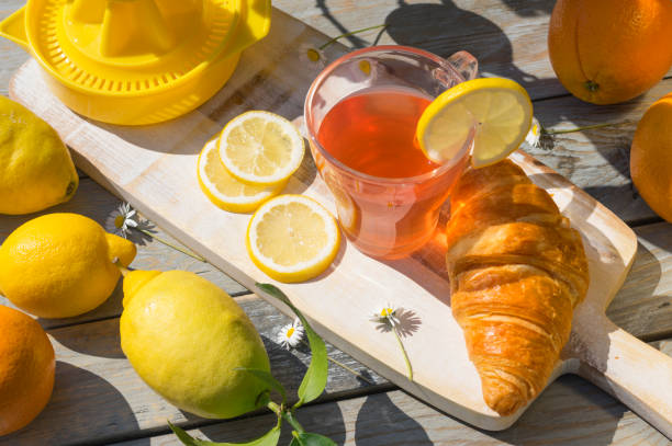 A cup of citrus fruit tea, croissant breakfast, lemons and oranges in the morning sunlight on wooden table stock photo