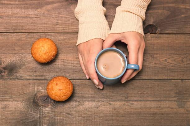 eine tasse kakao in den händen auf einem hölzernen hintergrund. helle pullover und mini-muffins. ansicht von oben - heiße schokoladen cupcakes stock-fotos und bilder