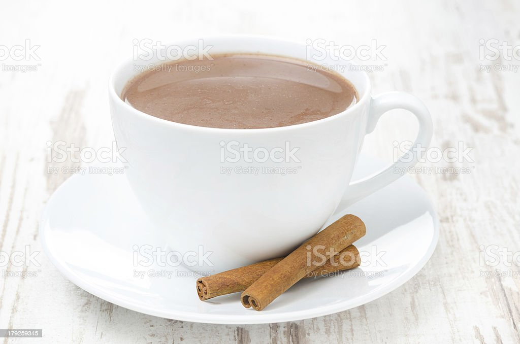cup of cocoa with cinnamon on a white table, horizontal royalty-free stock photo