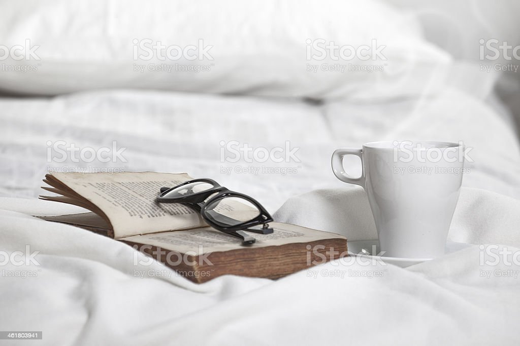 Cup of coffe, old book and glasses on white pillow. stock photo