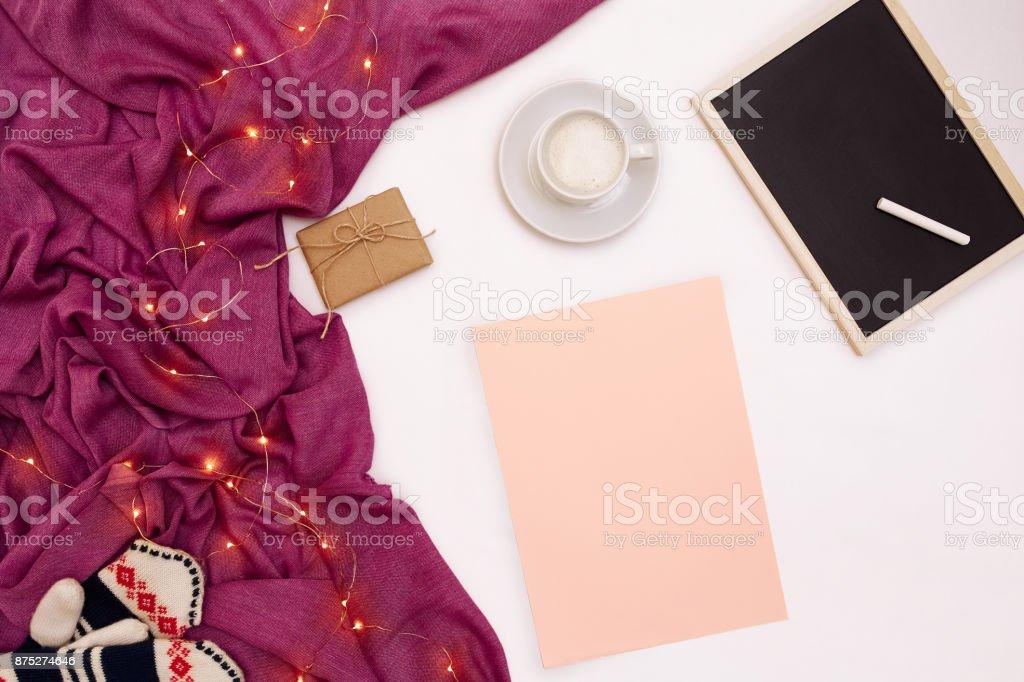 Uma xícara de café, uma pequena placa de madeira preta e um giz branco, papel rosa com metas de ano novo. Cachecol e Natal luzes no fundo branco - foto de acervo
