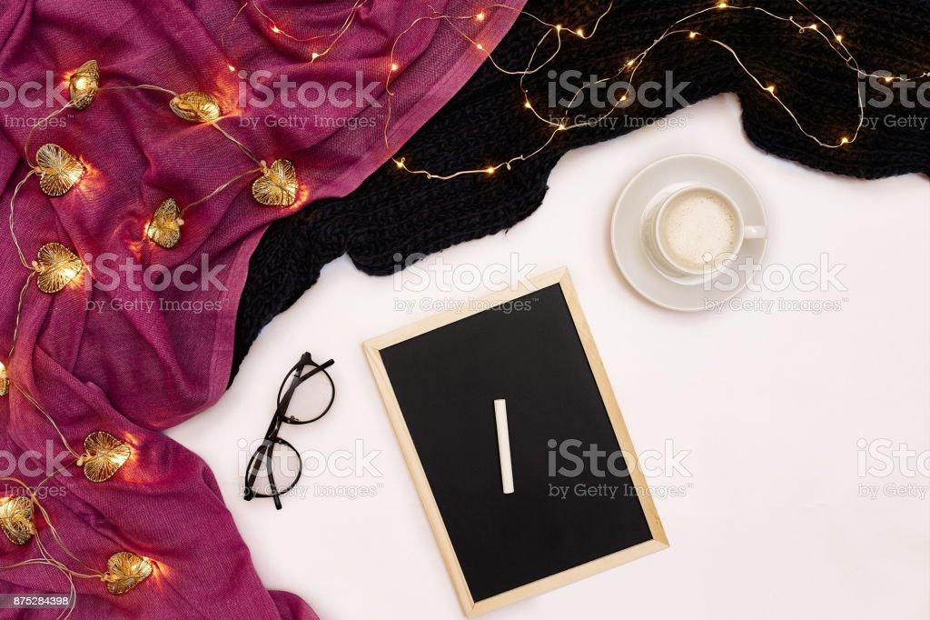 Uma xícara de café, uma pequena placa de madeira preta e um giz branco com metas de ano novo. Cachecol e Natal luzes no fundo branco - foto de acervo