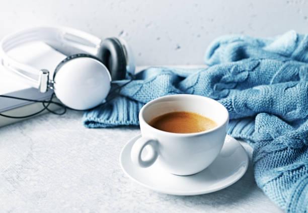 Tasse Kaffee, einem warmen blauen Tuch, Bücher und Kopfhörer auf grauem Hintergrund. – Foto