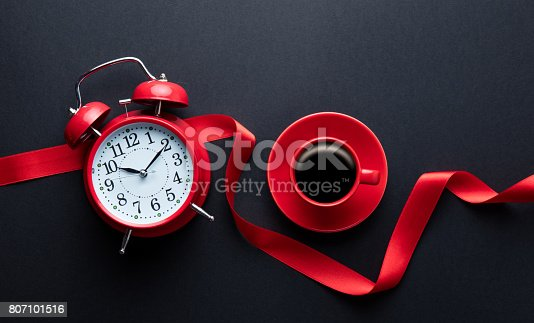 istock cup of coffee, alarm clock and ribbon 807101516