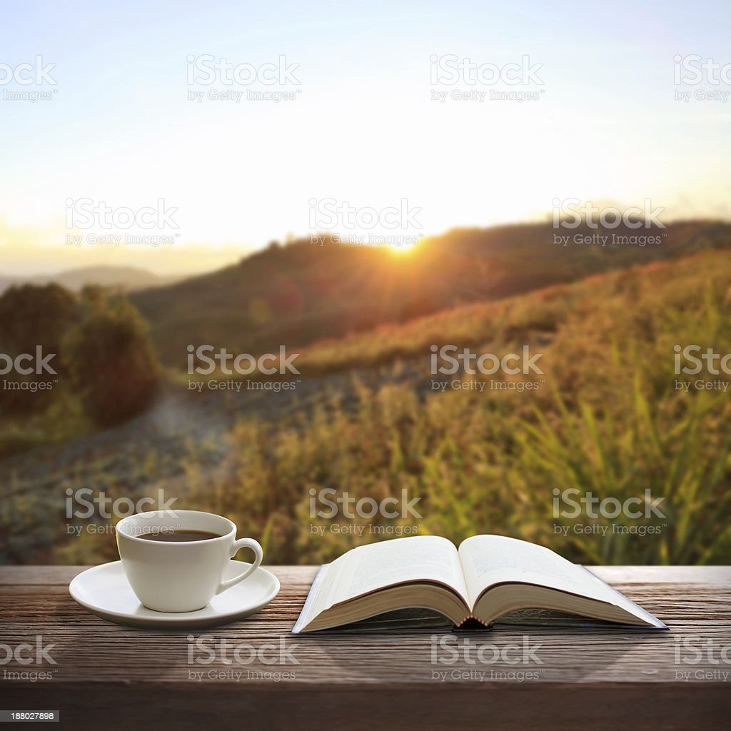 Cup of coffee and a book on wooden table stock photo