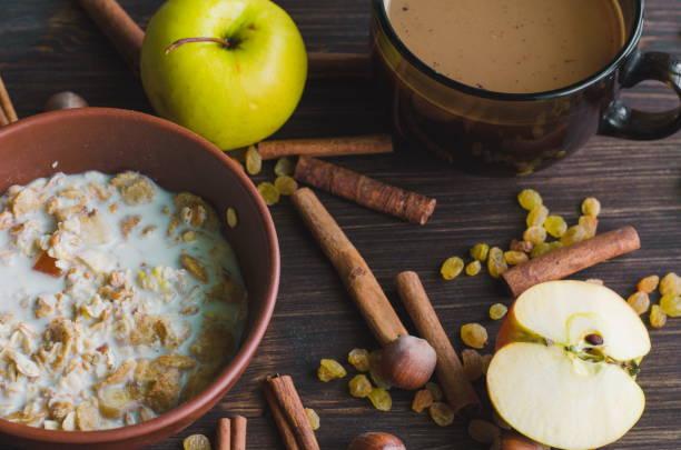 tasse kaffee und eine schale mit hafer-müsli für gesundes frühstück - haferflocken rosinen stock-fotos und bilder