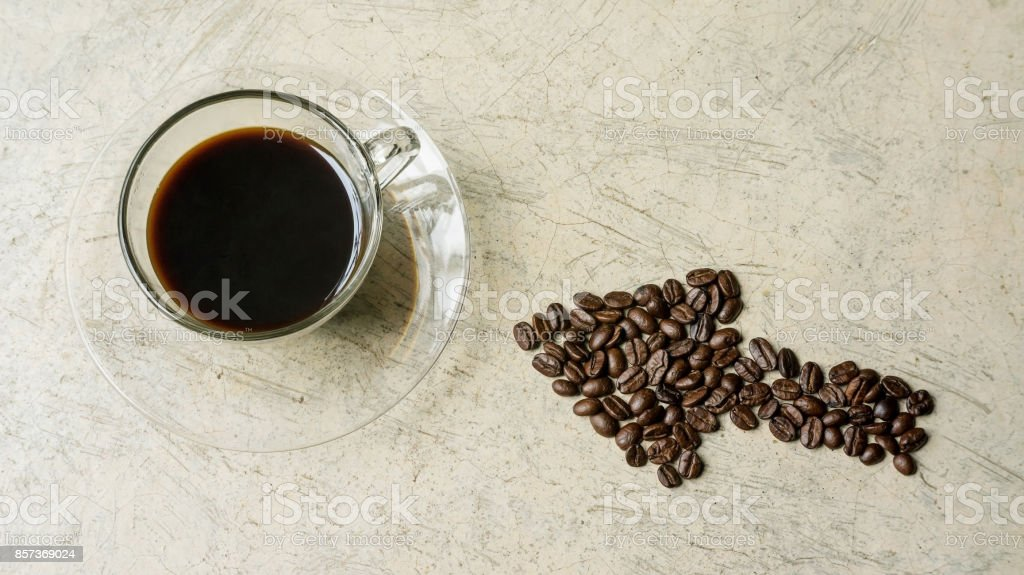 A cup of coffee and a coffee bean on a gray background. stock photo