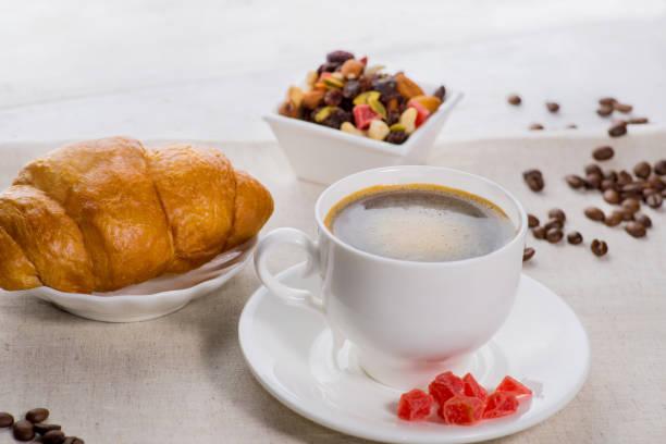 tasse kaffee und ein croissant auf einem bedienten tisch mit blütenknospen - heiße schokoladen cupcakes stock-fotos und bilder