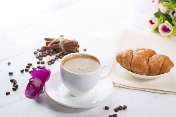 cup of coffee and a croissant on a served table with flower buds stock photo
