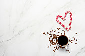 istock Cup of coffee and a heart-shaped caramel cane on a marble table. Concept dinner, valentines day, date, meeting, love of coffee, holiday, christmas eve. Flat lay, top view 1269271779