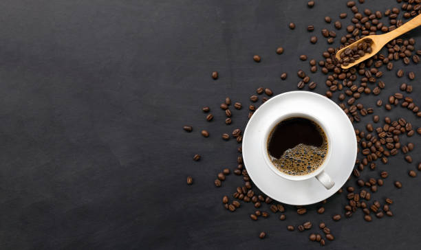 cup of coffee and bean on black wooden table background. top view – zdjęcie