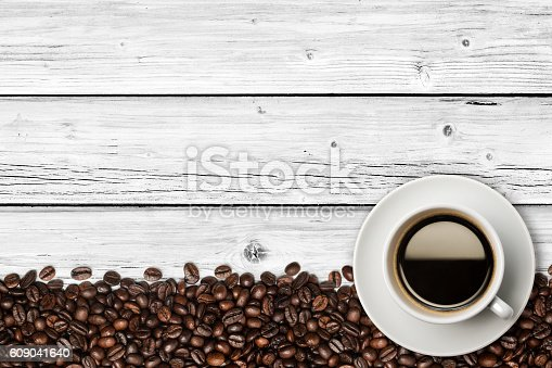 A cup of coffee on a weathered white wood table. Coffee beans are piled on making a line in the bottom of the photo. A wood grain pattern of table featuring even grains of wood running horizontally across the image. Compounds of the boards are clearly visible.