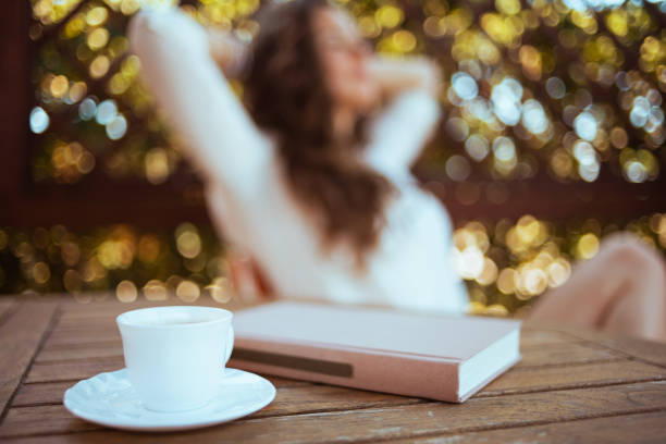 Cup of coffee and book at table and relaxed woman in background stock photo