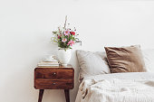 istock Cup of coffee and books on retro wooden bedside table. Rustic white ceramic vase with bouquet of pink cocmos and zinnia flowers. Beige linen and velvet pillows in bed. Scandinavian interior, bedroom. 1264970161