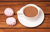 Cup of coffee and cakes on wooden background.