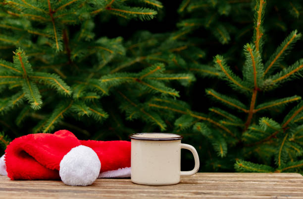 cup of coffee and Christmas hat on wooden table with spruce branches on background stock photo