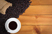 cup of coffee and coffee beans in a sack on wood background, top view.