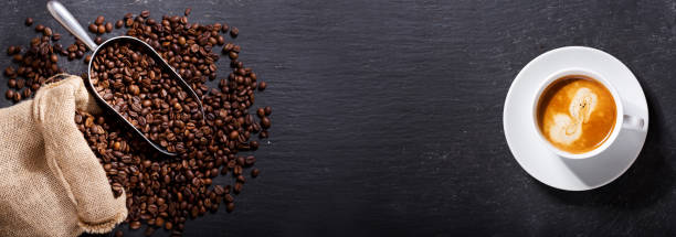 cup of coffee and coffee beans in a sack, top view - caffè foto e immagini stock