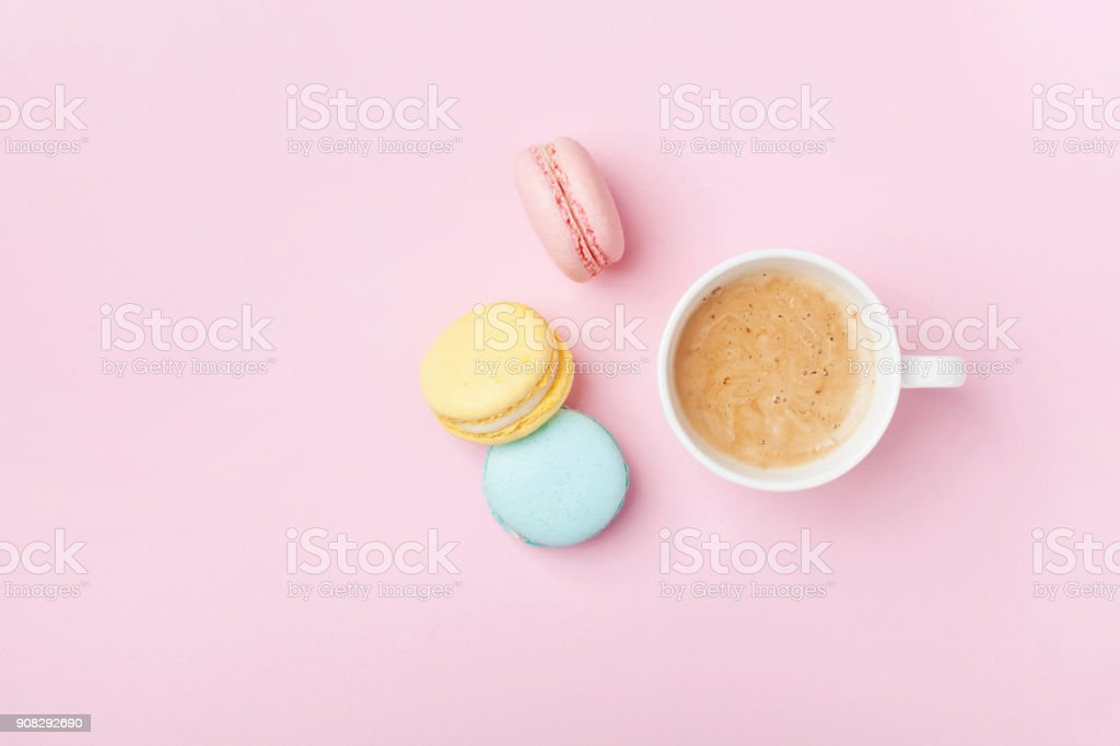 Cup of coffee and colorful macaron on pastel pink background top view. Cozy breakfast. Fashion flat lay.