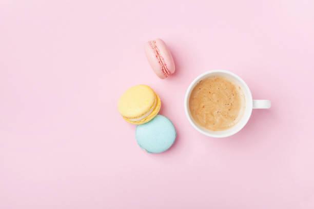 xícara de café e colorido macaron na vista superior fundo rosa pastel. aconchegante, café da manhã. leigos de forma plana. - macaroon - fotografias e filmes do acervo