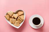 Cup of coffee and homemade cookies in plate shaped of heart on pink. Valentine card. Flat lay. View from above. Space for text.