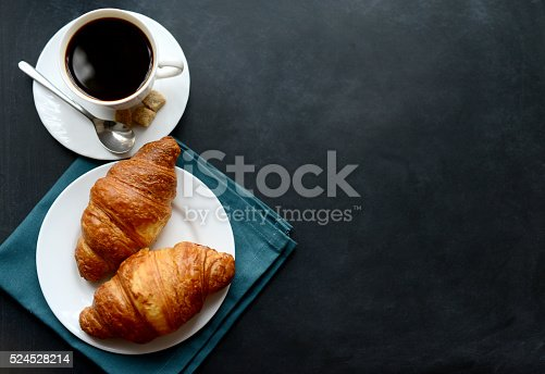 cup of coffee and croissants on black background