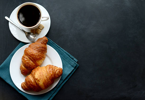 cup of coffee and croissants on black background cup of coffee and croissants on black background croissant stock pictures, royalty-free photos & images